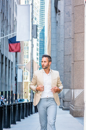Young handsome European Man with beard traveling in New York City. Young guy wearing beige blaze, white shirt, gray pant, walking on narrow vintage street with banners, looking around, thinking.