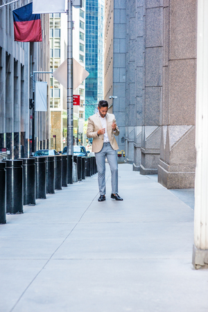 Thinking outside in New York City. Young European Man with beard, wearing beige blaze, white shirt, gray pant, black leather shoes, standing on narrow vintage street, lowering head, sad, thinking,