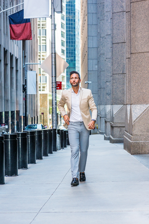 Young handsome European Man with beard traveling in New York City. Young guy wearing beige blaze, white shirt, gray pant, black leather shoes, walking on narrow vintage street with banners, cars. Banco de Imagens