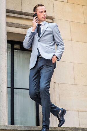 Junge Unternehmer Street Fashion in New York City. Mann trägt grauen Blazer, weißes Hemd, schwarze Krawatte, Hose, Lederschuhe, geht die Treppe durch das Fenster vor dem Bürogebäude hinunter und spricht mit dem Handy.