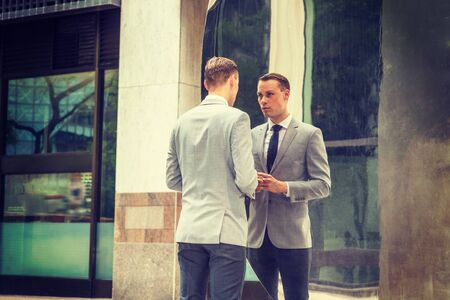 Young Businessman Fashion in New York City. Young Man wearing gray blazer, white shirt, black tie, black pants, standing on street in front of metal mirror, looking at reflections, thinking.