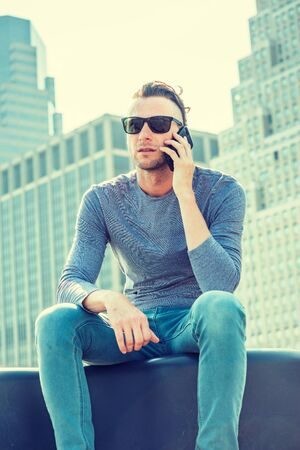 Young American Man traveling in New York City, wearing gray, long sleeve T shirt, sunglasses, sitting in front of business district with high buildings, talking on cell phone, looking, thinking. Reklamní fotografie