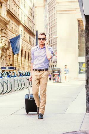 Young man traveling, working in New York, wearing light purple shirt, beige pants, black shoes, sun glasses, pulling rolling luggage, walking on old style street with high buildings, talking on phone. Stockfoto