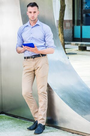 Young man reading outside in New York City, wearing light purple, long sleeve shirt, beige pants, black shoes, standing by silver metal wall on street, hands holding blue tablet computer, thinking.
