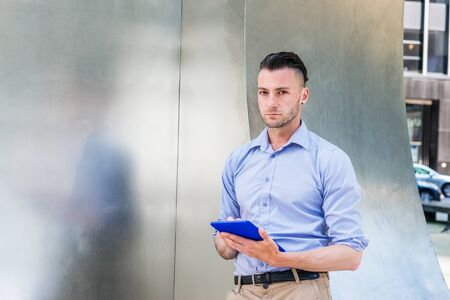 Modern Reading. Young handsome man wearing light purple, long sleeve shirt, standing by silver metal wall on street in New York City, hands holding blue tablet computer, reading, looking, thinking.