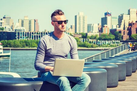 Young handsome American man traveling, working in New York City, wearing gray long sleeve T shirt, sunglasses, sitting by East River, working on laptop computer. Brooklyn buildings on background.