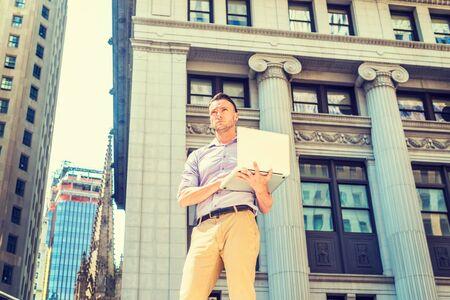 Young handsome man traveling, working in New York, wearing long sleeve shirt, beige pants, standing on street outside vintage office building, working on laptop computer, looking, thinking. Reklamní fotografie