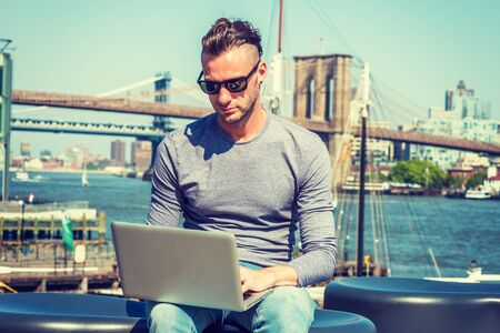 Young handsome American man traveling, working in New York City, wearing gray long sleeve T shirt, sunglasses, sitting by river, working on laptop computer. Brooklyn, Manhattan bridges on background.