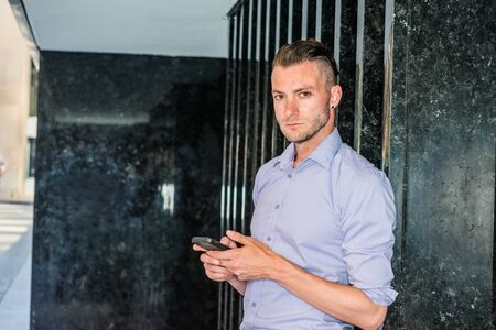 Young handsome man texting on cell phone outside office in New York City, wearing long sleeve, light purple shirt, standing on street against black marble wall, hands holding cell phone, looking away.