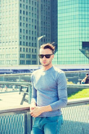 Young handsome Man traveling in New York City, wearing gray, long sleeve T shirt, sunglasses, standing at park in business district with high building, under sun, looking around, relaxing, thinking. Reklamní fotografie