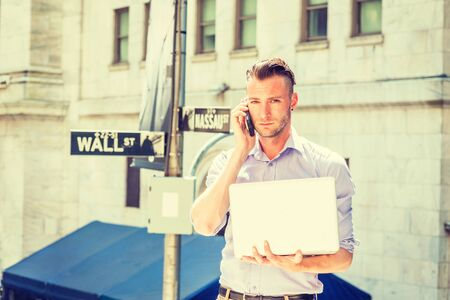 Young handsome man traveling, working in New York City, wearing long sleeve, light color shirt, standing outside office by Wall Street sign under sun, working on laptop computer, talking on cell phone
