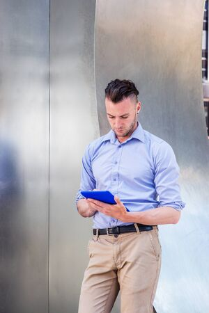 Modern Reading. Young handsome man wearing light purple, long sleeve shirt, beige pants, standing by silver metal wall on street in New York City, looking down, reading blue tablet computer.