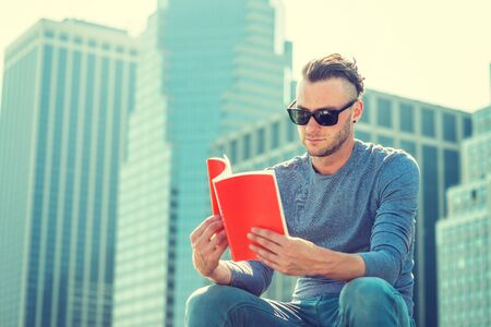 I love reading book. Young American Man wearing gray, long sleeve T shirt, sunglasses, sitting in front of business district with high buildings in New York City, under sun, reading red book.