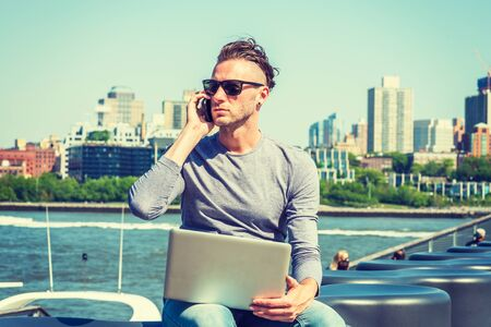 Young American man traveling, working in New York, wearing gray, long sleeve T shirt, sunglasses, sitting by river, working on laptop computer, talking on cell phone. Brooklyn buildings on background.