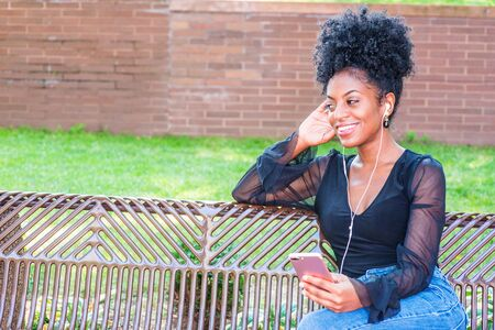 Young beautiful African American Woman with afro hairstyle wearing mesh sheer long sleeve shirt blouse, sitting on bench at park in New York, listening music with earphone and cell phone, thinking. Stock fotó