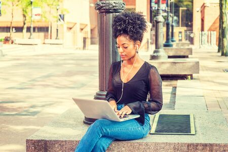 Young African American Woman with afro hairstyle wearing mesh sheer long sleeve shirt, jeans, sitting by light pole on campus in New York, listening music with earphone, working on laptop computer