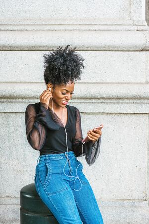 Young African American Woman with afro hairstyle, wearing mesh sheer long sleeve shirt blouse, blue jeans, sitting on street in New York City, listening music with earphone and cell phone, texting. Archivio Fotografico