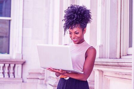 Młoda kobieta Afroamerykanów z fryzurą afro na sobie top bez rękawów, stojąc w biurowcu w Nowym Jorku, patrząc w dół, pracując na komputerze przenośnym, uśmiechając się. Kolor Proton Purple filtrowany wygląd. Zdjęcie Seryjne
