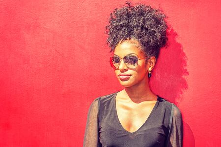 Portrait of Young African American Woman in New York City. Young black woman with afro hairstyle wearing long sleeve mesh sheer shirt, sunglasses, standing against red background under sun.