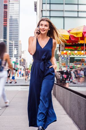 Young Eastern European Woman with long brown hair traveling in New York, wearing blue sleeveless V neck jumpsuit, walking on street with high buildings in middletown of Manhattan, talking on phone. Reklamní fotografie