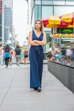 Young Eastern European Woman traveling in New York, wearing blue sleeveless jumpsuit, black leather shoes, crossing arms, looking around,  walking on busy street in middletown of Manhattan. Reklamní fotografie