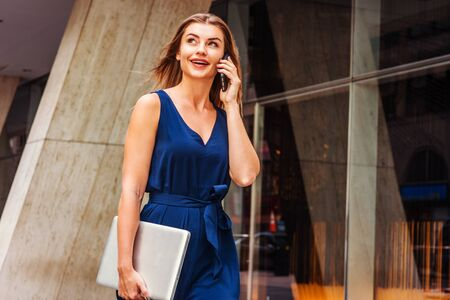 Young Eastern European American Woman talking on cell phone, traveling, working in New York City, wearing blue sleeveless jumpsuit, carrying laptop computer, walking on street outside office building. Reklamní fotografie