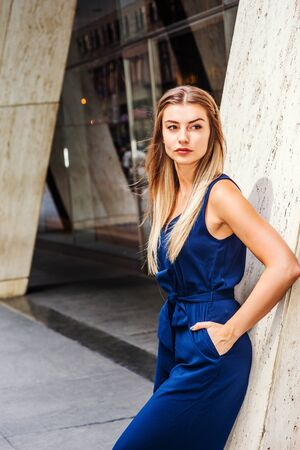 Street Fashion in New York. Young Eastern European American Woman with long brown hair, wearing blue sleeveless fashionable jumpsuit, standing against column outside office building, taking work break. Stock Photo