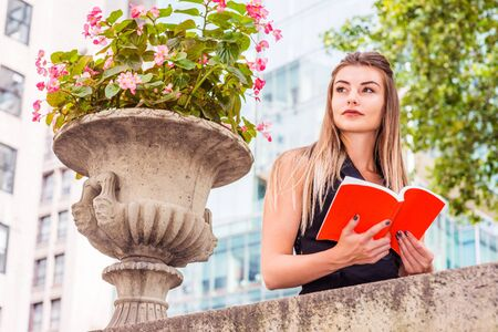 Young Eastern European American College Student studying in New York, wearing black sleeveless blazer vest dress, standing by top of wall on campus, hands holding red book, looking up, thinking.