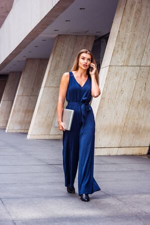 Young Eastern European American Woman talking on phone, traveling, working in New York, wearing blue jumpsuit, black leather shoes, carrying laptop computer, walking on street outside office building. Reklamní fotografie
