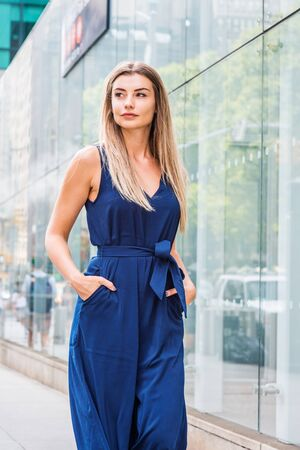 Young Eastern European Woman with long brown hair traveling in New York, wearing blue sleeveless jumpsuit, hands in pockets, walking on street by glass wall with reflections in Manhattan, New York.