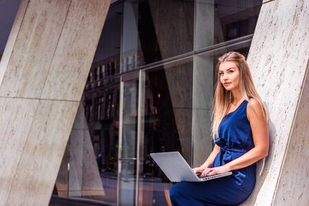 Young Eastern European American Woman working in New York City, wearing blue sleeveless jumpsuit, standing against column outside office building, working on laptop computer, looking up, thinking.
