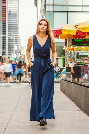 Young Eastern European Woman with long brawn hair traveling in New York City, wearing blue sleeveless, v neck, jumpsuit, black leather shoes, walking on busy street in middletown of Manhattan. Stock Photo