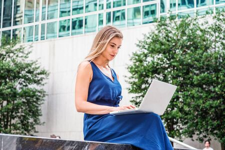 Way to Success. Young Beautiful  Eastern European American Woman studying in New York, wearing blue sleeveless jumpsuit, sitting outside on campus, looking down, reading, working on laptop computer.