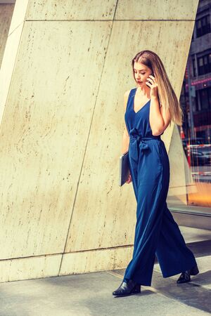 Young Eastern European American Woman talking on phone, traveling, working in New York, wearing blue jumpsuit, black leather shoes, carrying laptop computer, walking out from office building to street