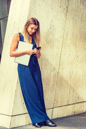 Young Eastern European American Woman with long brown hair, wearing blue sleeveless jumpsuit, black leather shoes, holding laptop computer, standing against column in New York, texting on cell phone.