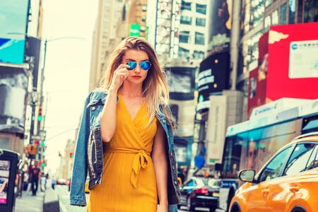 Young Eastern European Woman traveling in New York, with long brown hair, wearing yellow dress, blue Denim jacket draped over shoulder, blue sunglasses, walking on street in Times Square of Manhattan.