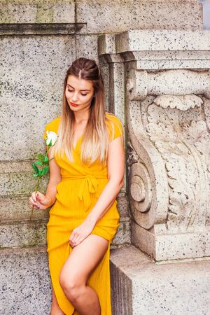 Lonely young Eastern European American girl missing you in New York, wearing yellow short sleeve long dress, standing at corner against wall on campus, holding white rose flower,  looking, thinking.