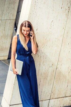 Young Eastern European American Woman with long brown hair, wearing blue sleeveless jumpsuit, holding laptop computer, standing against column outside office in New York, talking on cell phone.