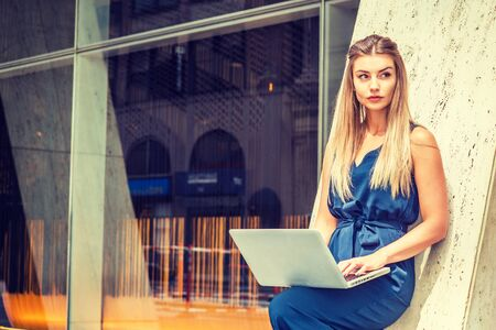 Young Eastern European American Woman working in New York, wearing blue sleeveless jumpsuit, standing against column outside office building, bending leg, working on laptop computer, looking away.