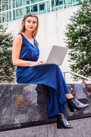 Way to Success. Young Eastern European American Woman studying in New York, wearing blue sleeveless jumpsuit, black leather shoes, sitting outside on campus, working on laptop computer, looking away.