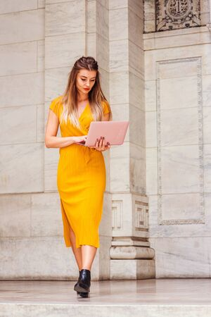 Way to Success. Young Eastern European American woman studying in New York, with long brown hair, wearing yellow short sleeve long dress, working laptop computer, walking out from office building.