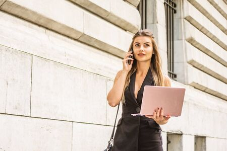 Way to Success. Young Eastern European American Woman studying, working in New York, wearing black sleeveless blazer vest dress, walking on campus, working on laptop computer, talking on cell phone.