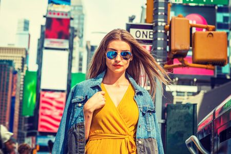 Young Eastern European Woman traveling in New York, with long brown hair, wearing yellow dress, blue Denim jacket draped over shoulder, blue sunglasses, standing on street in Times Square of Manhattan.