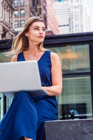 Way to Success. Young Eastern European American Woman studying in New York, wearing blue sleeveless jumpsuit, sitting on street outside school, working on laptop computer, looking away, thinking. Reklamní fotografie