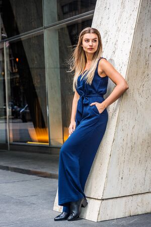 Street Fashion in New York City. Young Eastern European American Woman with long brown hair, wearing blue sleeveless jumpsuit, black leather shoes, standing against column outside, taking work break.