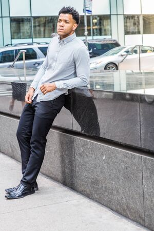 Young Mix Race American Man traveling, relaxing in New York City, wearing light gray long sleeve shirt, black pants, leather shoes, standing by half marble wall on street, looking up, thinking.