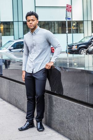 Young Handsome American Man traveling, relaxing in New York City, wearing light gray long sleeve shirt, black pants, leather shoes, standing by half marble wall on street, confidently looking forward. Reklamní fotografie