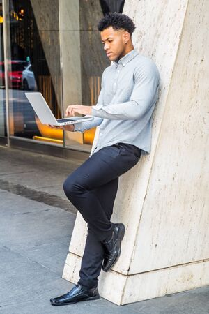Young Mix-Race American Man working on laptop computer outside office in New York City, wearing light gray long sleeve shirt, black pants, leather shoes, standing on street, looking down, typing.