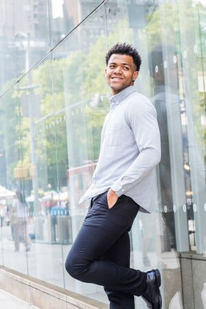 Young Mix Race American Man wearing light gray, long sleeve shirt, black pants, hand in pocket, standing against glass wall with reflections on street in Midtown of Manhattan, New York City, smiling. Stock Photo