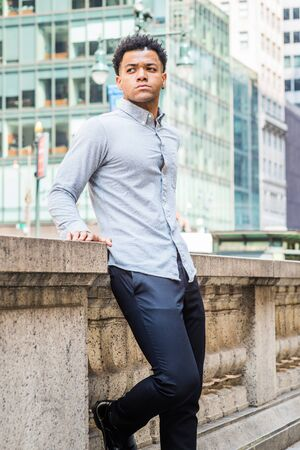 Portrait of Young Handsome American Man in New York City, wearing light gray long sleeve shirt, black pants, standing by half wall outside office building on street in Manhattan, looking forward.
